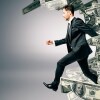 Running businessman with dollar banknote wave ob grey background. Success and wealth concept