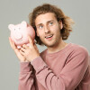 Handsome man with piggy bank on grey background