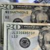 UKRAINE - 2020/02/27: In this photo illustration twenty US dollar banknotes are seen displayed. (Photo Illustration by Sergei Chuzavkov/SOPA Images/LightRocket via Getty Images)